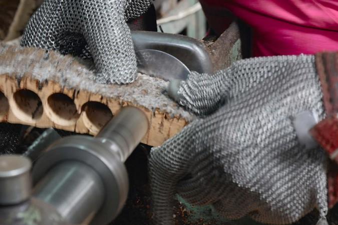 Es braucht geübte Fachleute, die das Maximum an intakten Korken aus der wertvollen Rinde stanzen. Die Metallhandschuhe schützen vor Verletzungen.